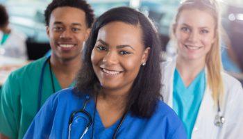 African American male, African American female and Caucasian female healthcare providers attend conference.